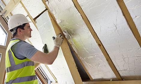 man voegt isolatie toe tijdens zolder verbouwing